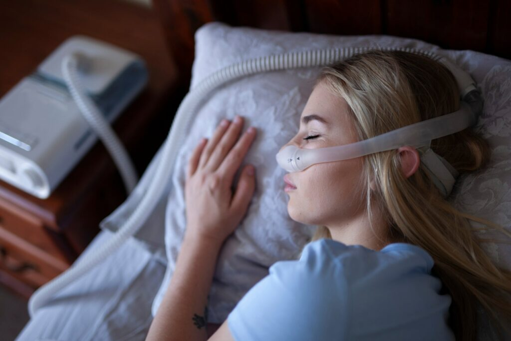 woman sleeping soundly wearing a cpap therapy machine